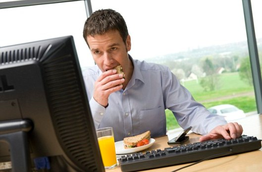 Male office worker eating lunch at computer